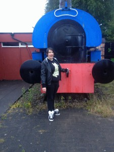 I made Kate stop in the rain so I could take this pic of her with a train.